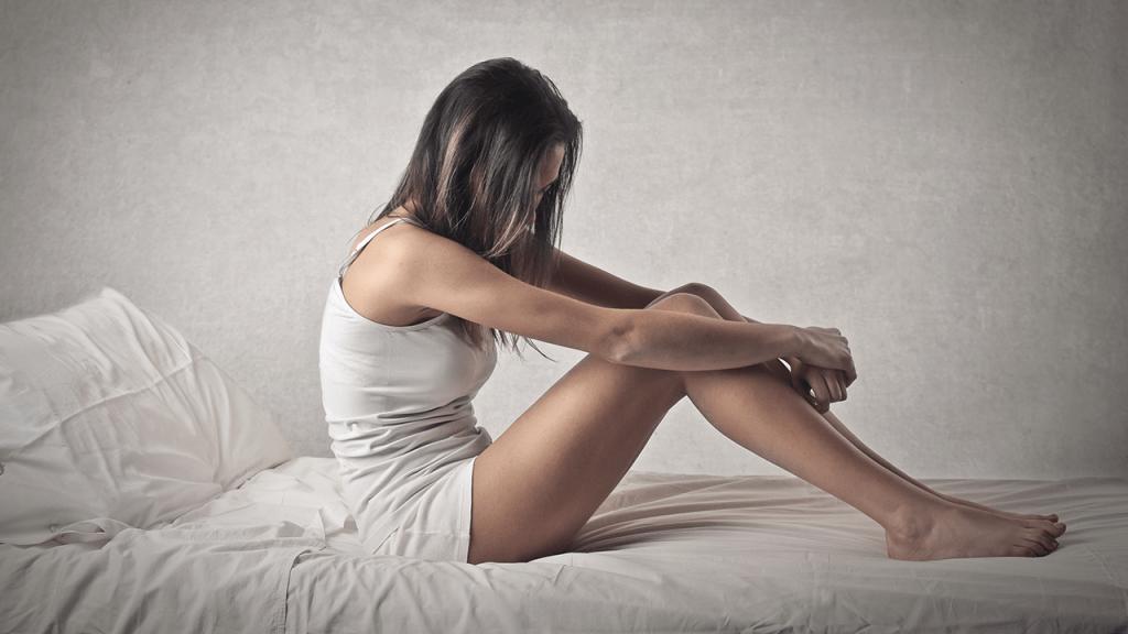 sad woman on bed
